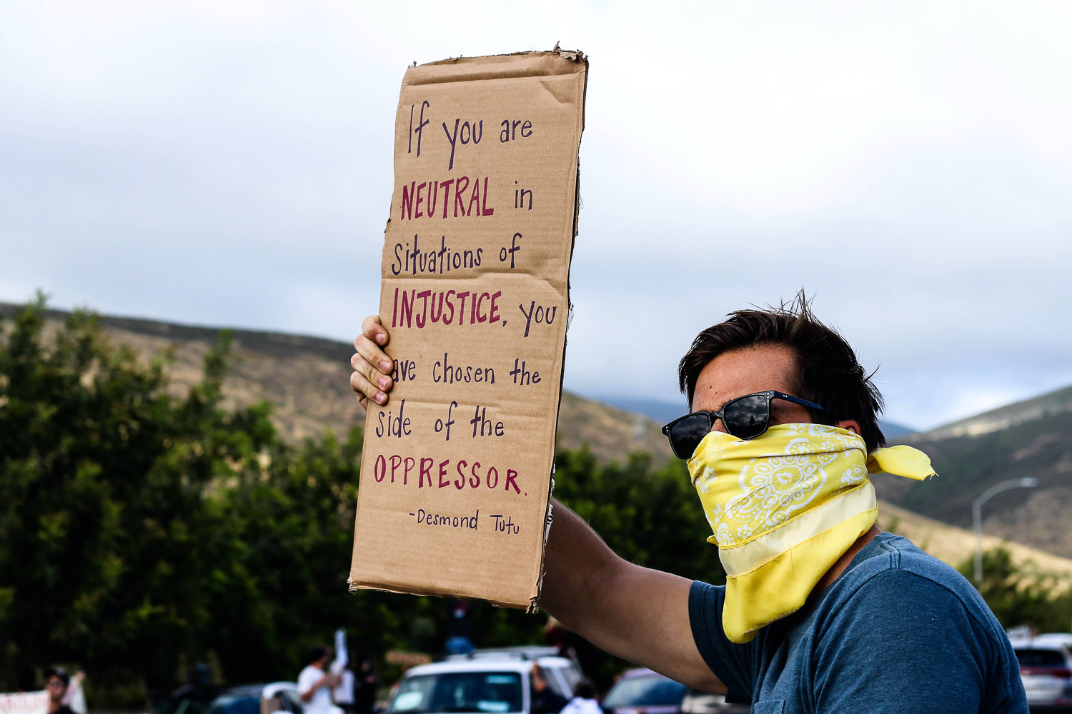 Protester wearing a mask and holding a sign