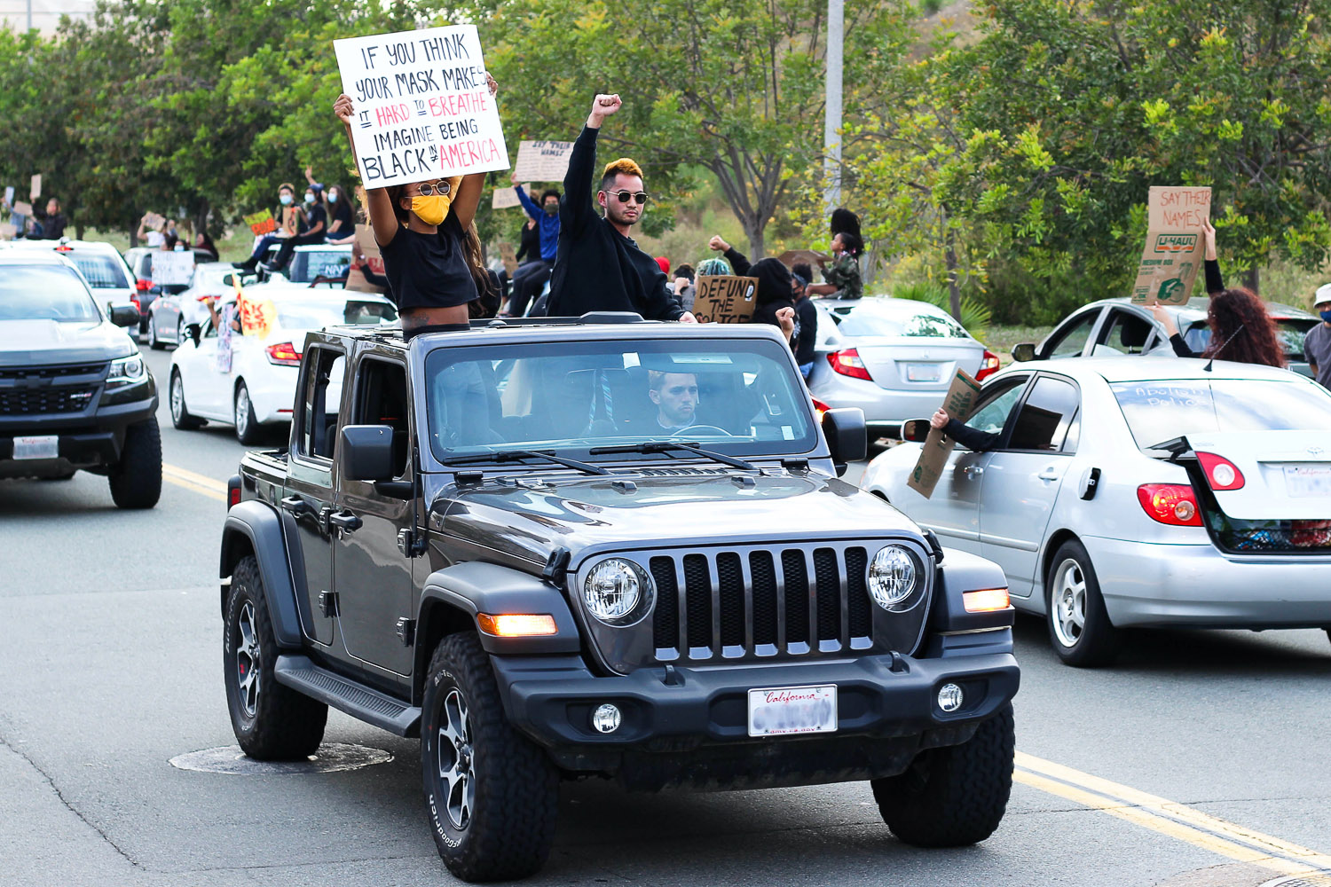 Two protesters in black Jeep